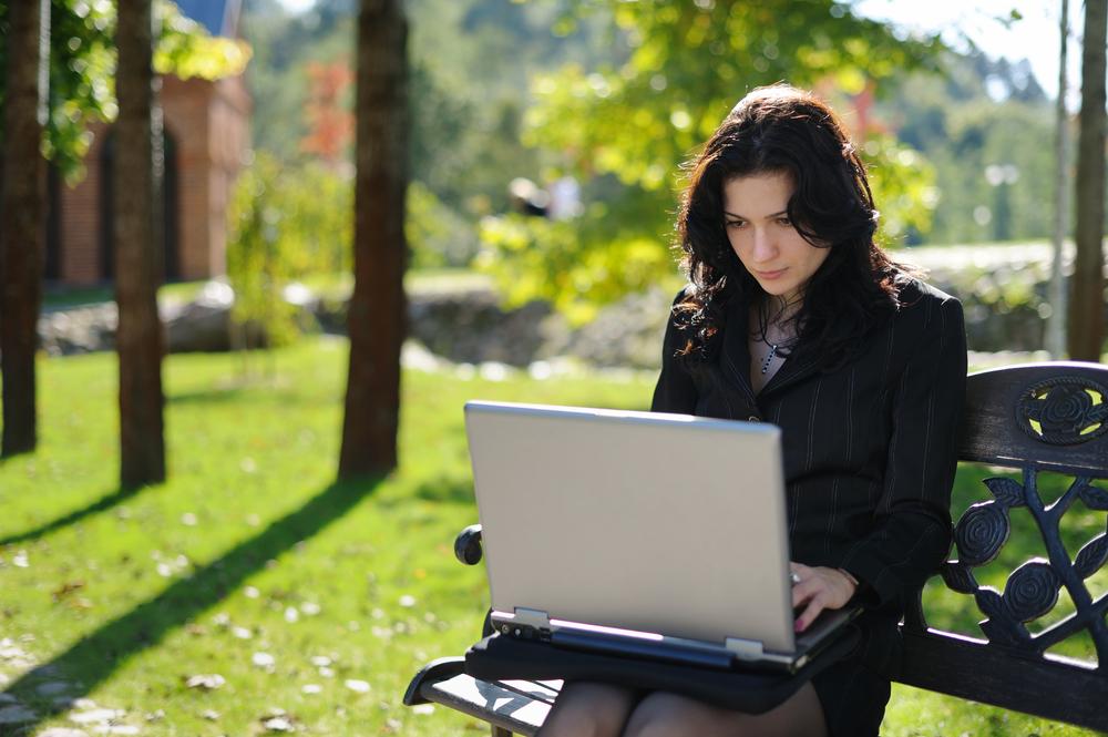 Kobieta korzystający z Wi-Fi w parku, fot. shutterstock.com