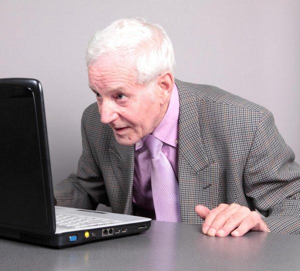 Zdziwiony starszy człowiek przed komputerem